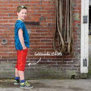 Jongen in t-shirt en korte joggingbroek van Dress en Les - zijkant